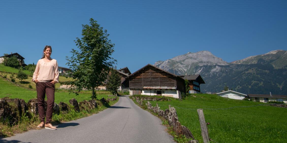 Priska Grünenfelder steht seitlich der Strasse welche an alten Häusern vorbei zu den Bergen führt.